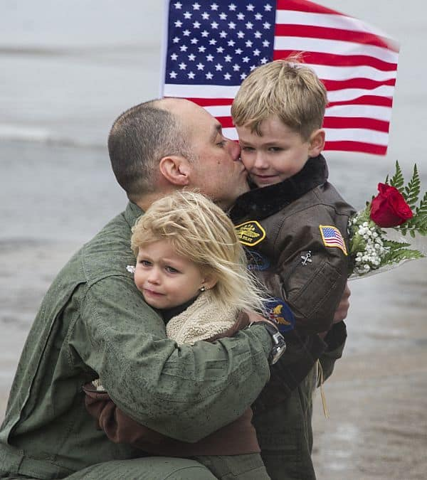 """151122-N-YR571-153 VIRGINIA BEACH, Va. (Nov. 22, 2015) A pilot assigned to Strike Fighter Squadron (VFA) 136, the """"Knighthawks,"""" hugs his kids during the squadron's homecoming. The squadron returned as part of Carrier Air Wing (CVW) 1 following a more than nine-month deployment aboard the aircraft carrier USS Theodore Roosevelt (CVN 71). (U.S. Navy photo by Mass Communication Specialist 2nd Class Kevin F. Johnson/Released)"""