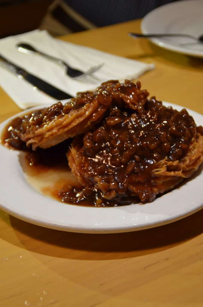 wo crunchy churros topped with a caramelized pecan sauce of raw pecans at Hugo's Restaurant. Traveling Well For Less