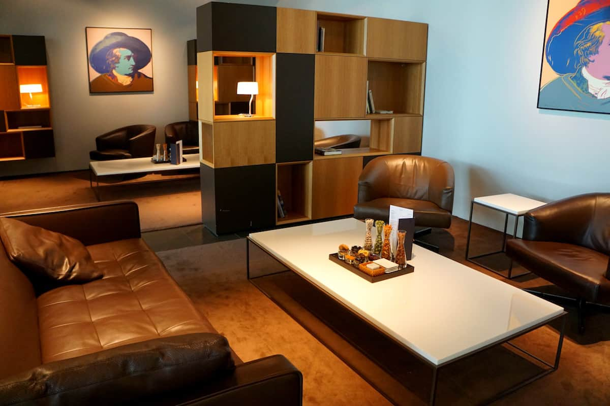brown leather chairs and couch, wooden bookcase in airport lounge