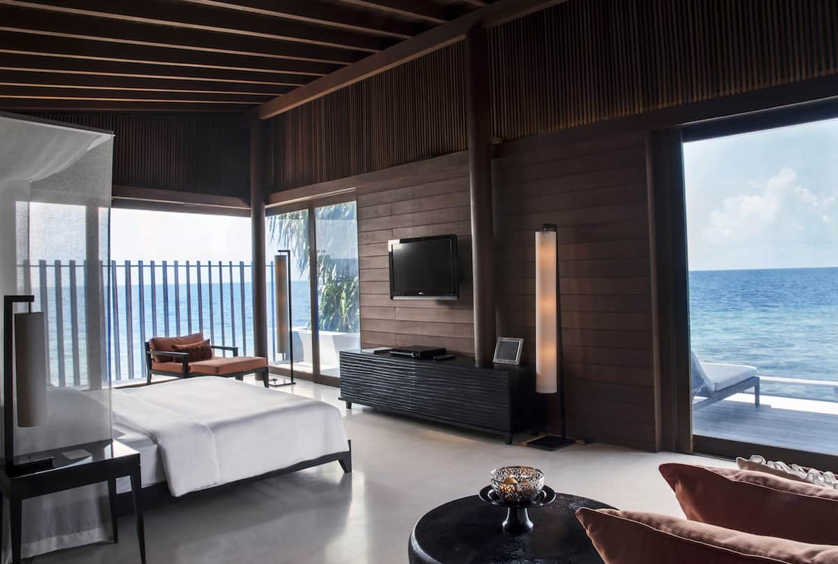 Bed and living area of Park Hyatt Maldives Hadahaa overwater bungalow.