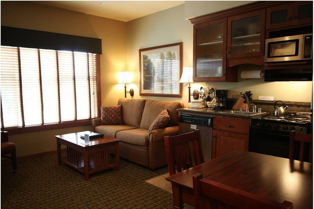 Living area and kitchen in Homestead Resort room. The Homestead Resort offers 30 studio, 1 bedroom, and 2 bedroom suites on the golf course overlooking the lake. #lynden #washington #travel #hotel https://www.travelingwellforless.com