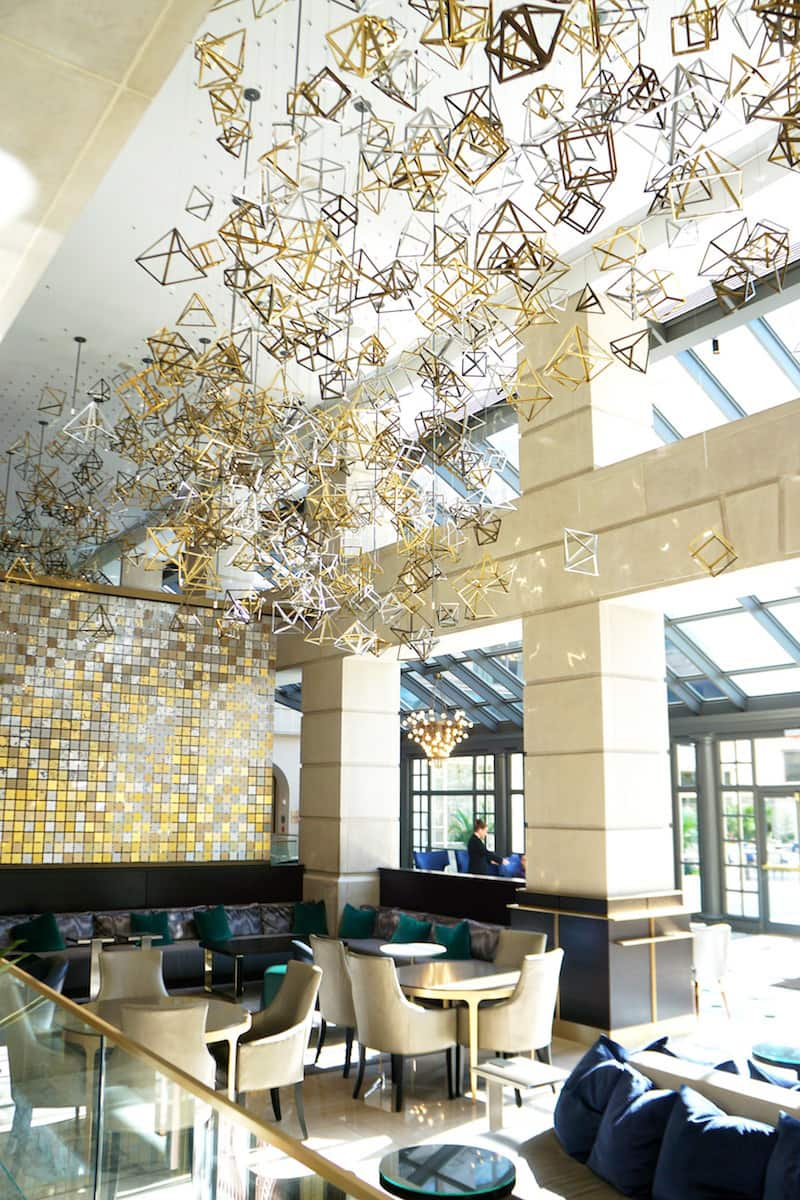 The lobby of the Fairmont Washington DC is an explosion of metal. The tri-colored geometric charms take your breath away. Can you guess the number of charms? | Fairmont Washington DC | Fairmont Gold | luxury hotel | where to stay in Washington DC | TravelingWellForLess.com
