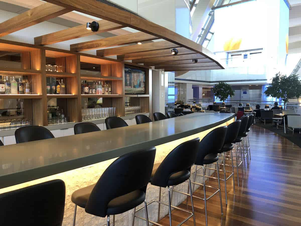 bar seating at outdoor bar overlooking atrium Star Alliance Business Class Lounge LAX