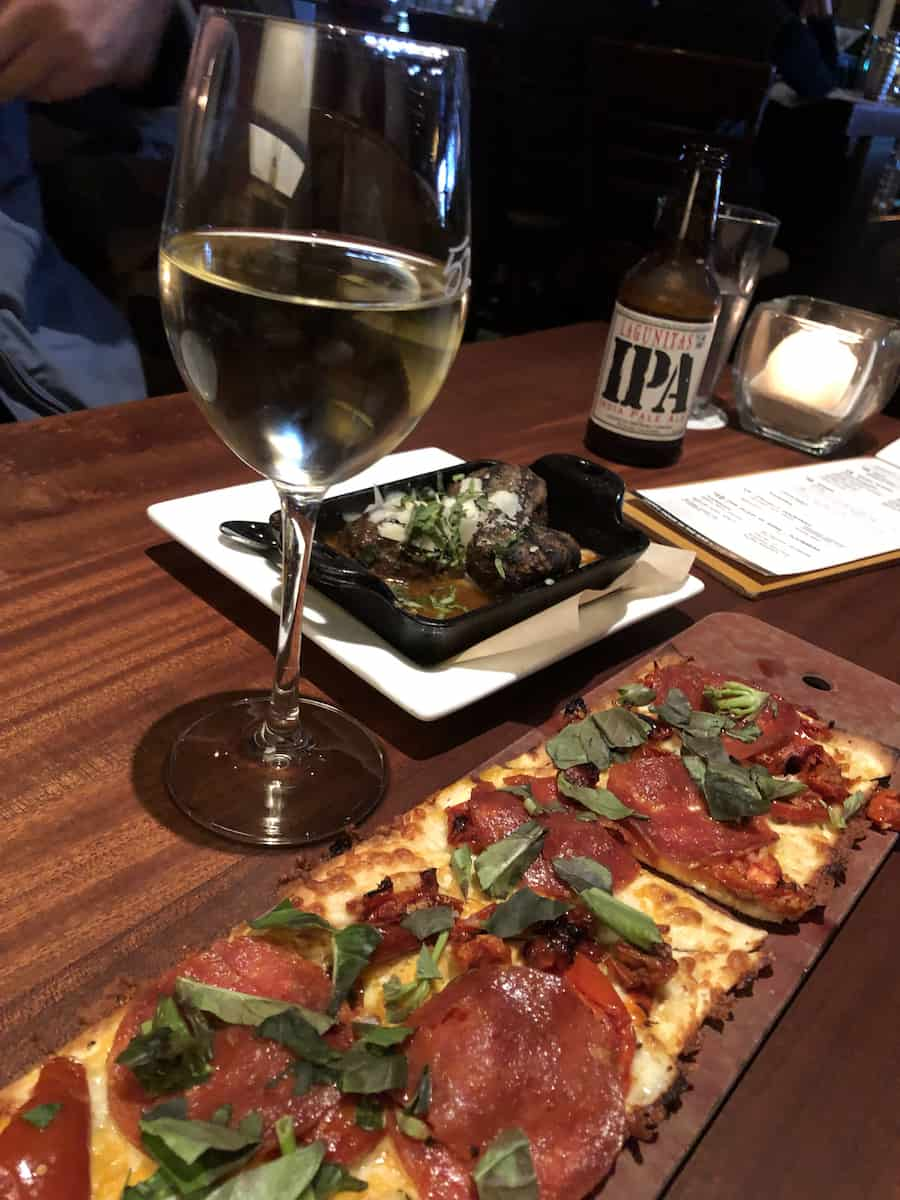 Pepperoni flatbread pizza, glass of white wine, meatballs, and IPA beer during Happy Hour at Seasons 52 South Coast Plaza, one of the best things to do in Costa Mesa