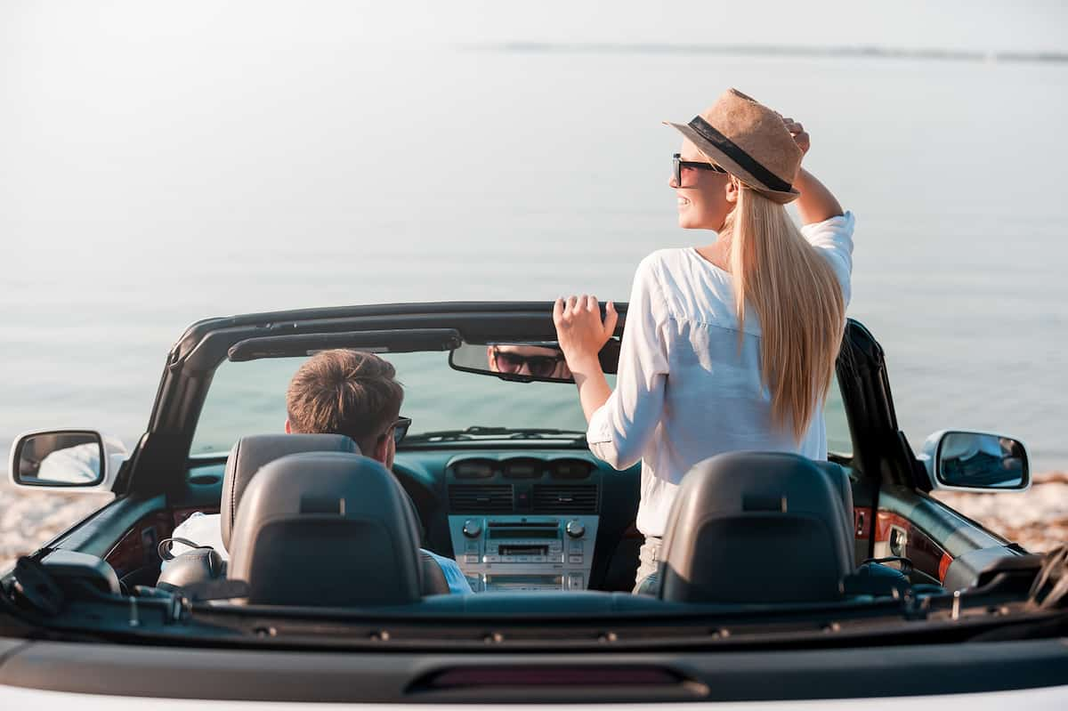 Rear view of smiling young woman enjoying scenery while her boyfriend sitting near on front seat of their convertible