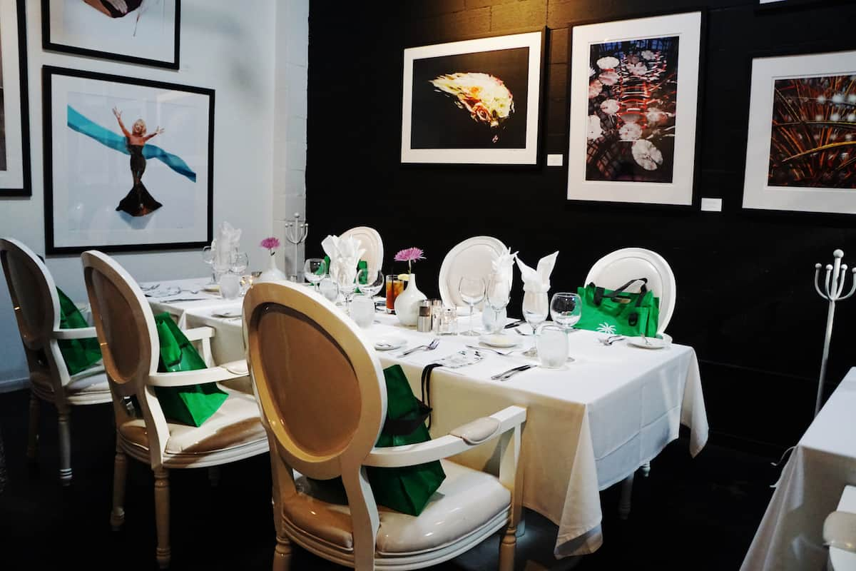 chic restaurant with white furniture black wall and celebrity photographs