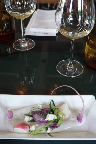 pink purple radishes in dressing on a white plate with a glass of white wine