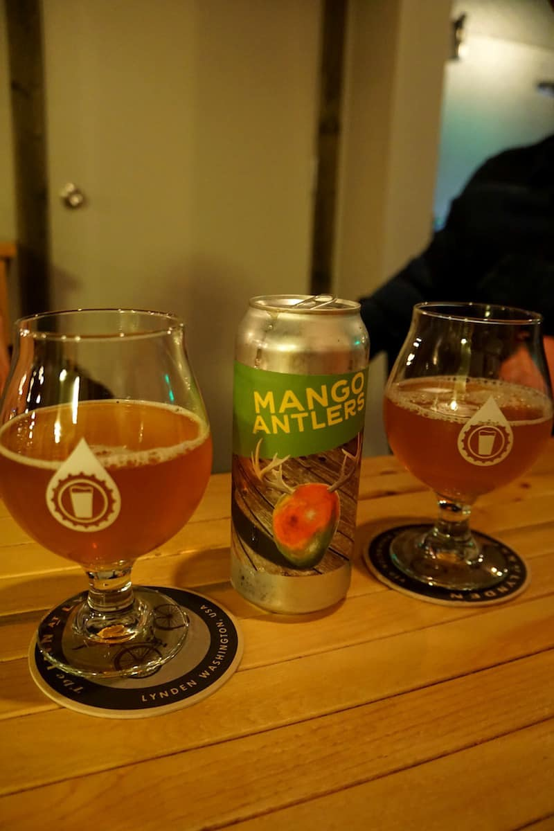 Two pint glasses and a can of Mango Antlers IPA. Overflow taps is your Lynden source for high-quality craft beer not found in the grocery stores. #craftbeer #thingstodoinLynden #Lynden #Washington