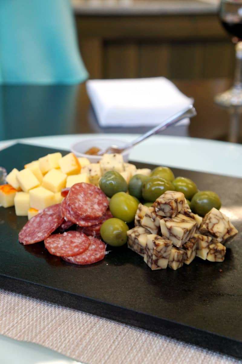 A charcuterie plate of two cheeses, salami, and olives at Twin Sisters Creamery. Looking for the best things to do in Lynden? Visit Twin Sisters Creamery and try over 7o types of cheese including Whatcom Blue. #cheese #charcuterie #thingstodoinLynden #Lynden #Washington