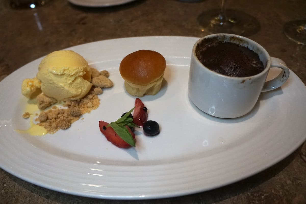 vanilla ice cream, muffin, cup of chocolate souffle on white plate