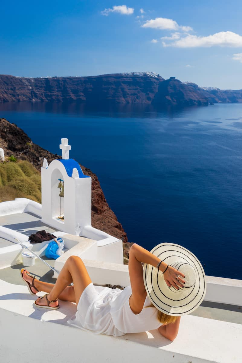 woman in white dress and white hat lounging on while building overlooking deep blue sea