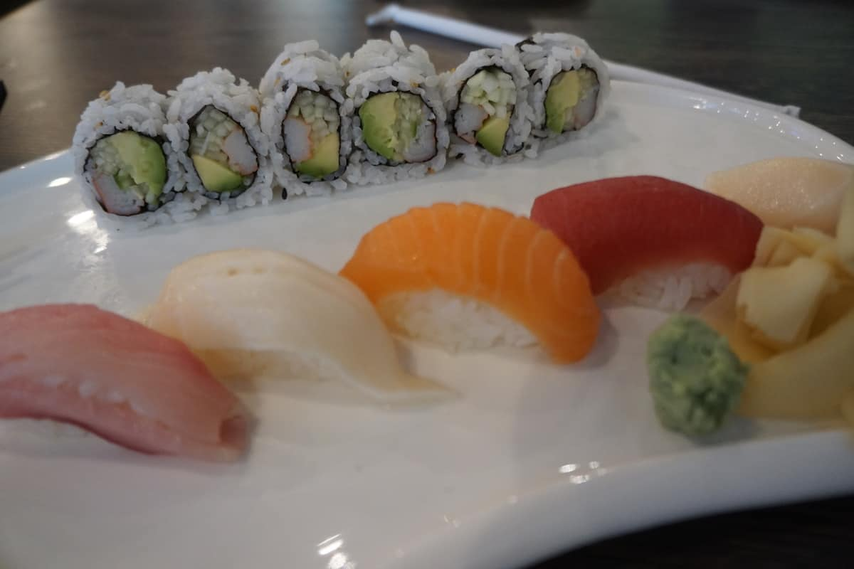 six piece california roll with five pieces of sushi on white plate
