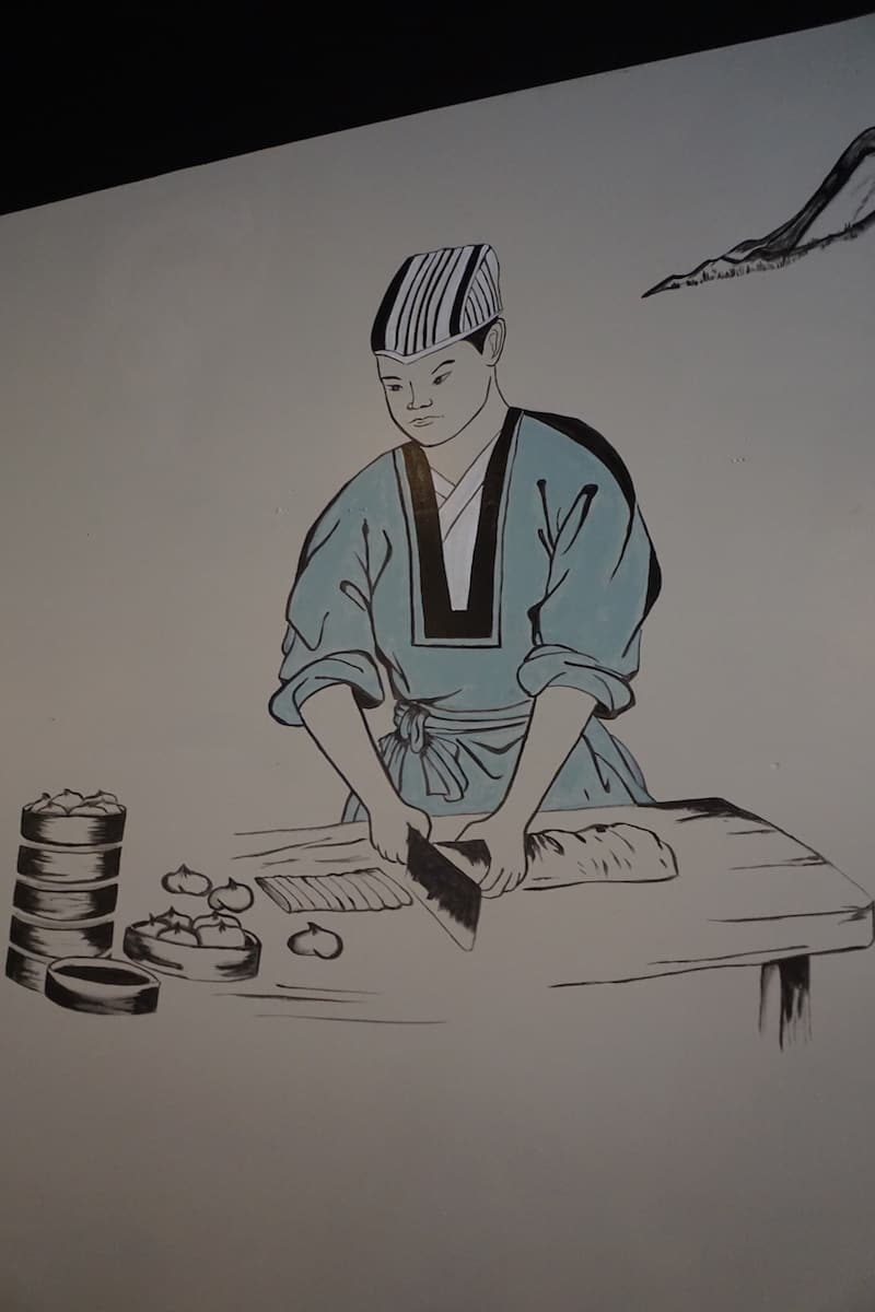 black and white mural of Japanese chef in teal coat making dumplings