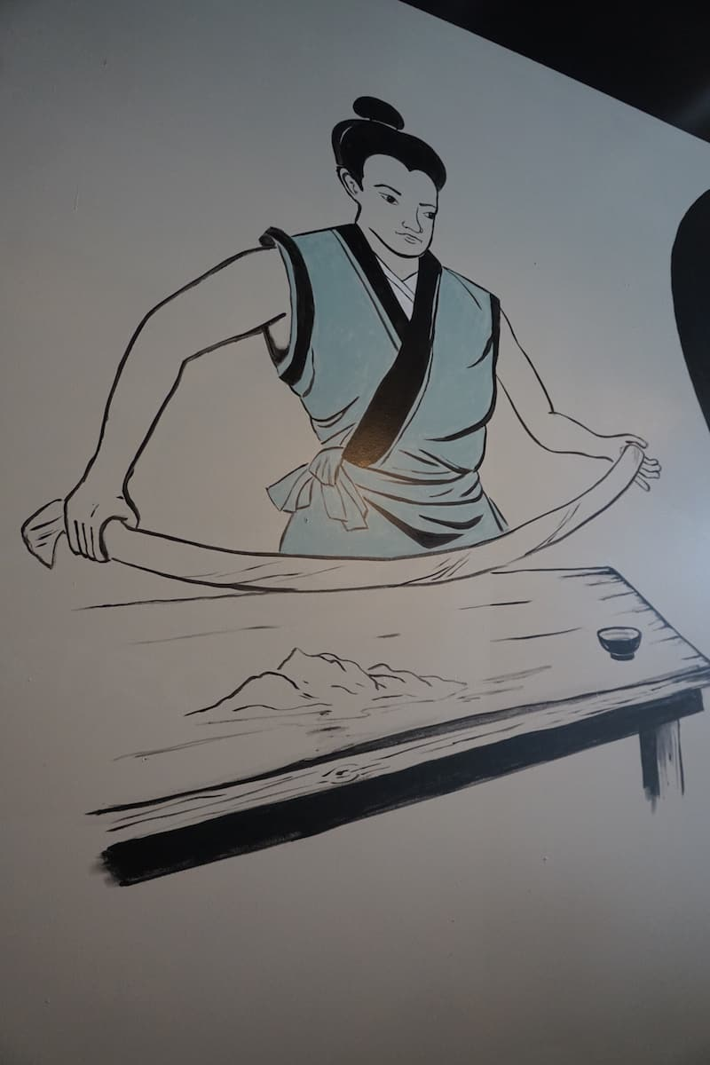 black and white mural of Japanese chef in teal coat making noodles by hand