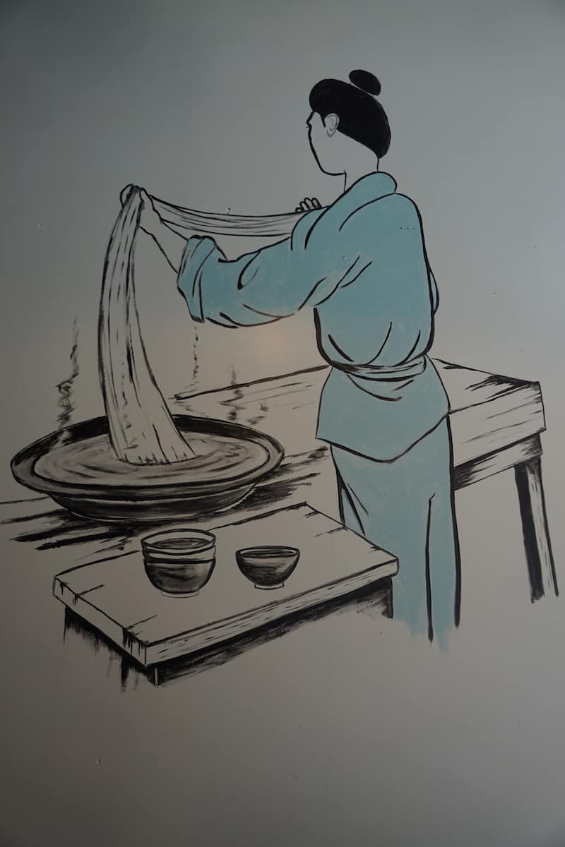 black and white mural of Japanese chef in teal coat making ramen