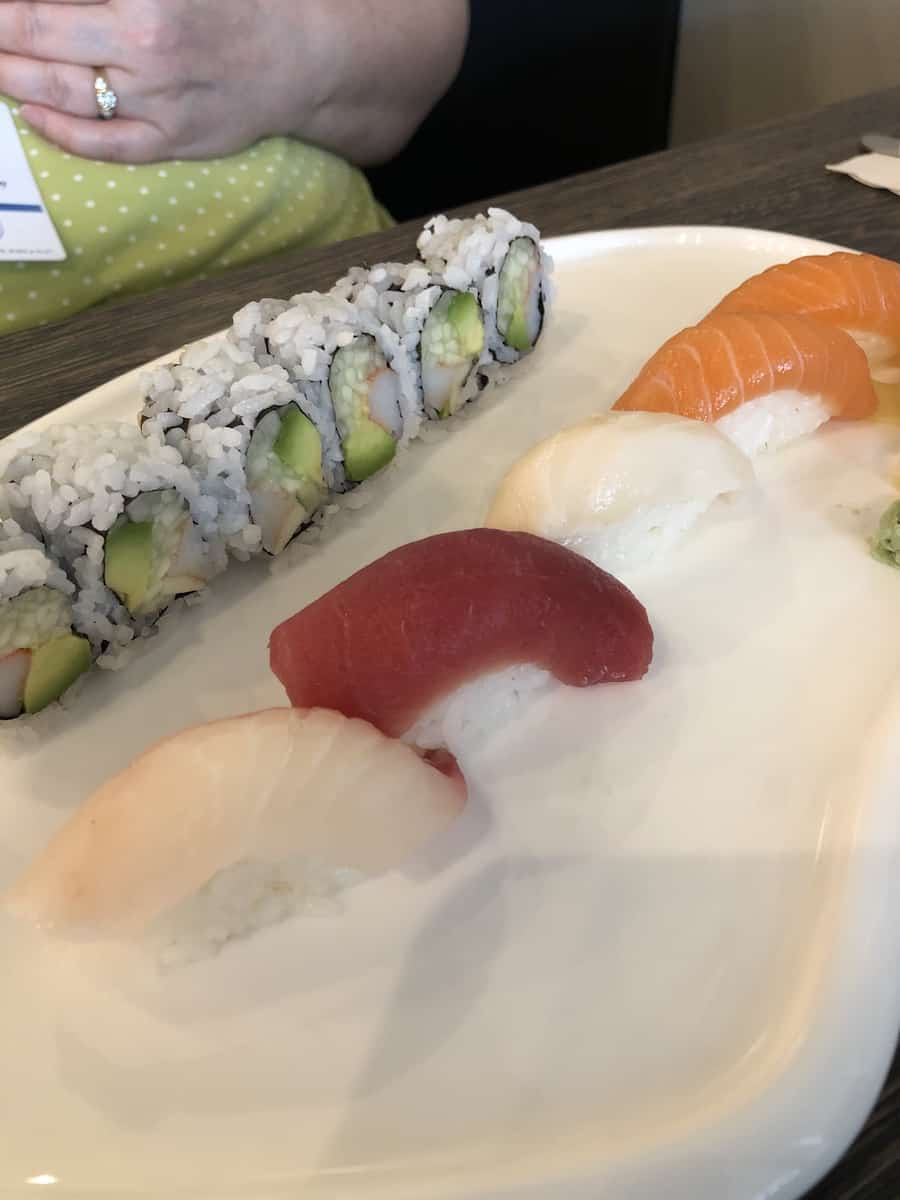 california roll and five pieces of sushi on white plate