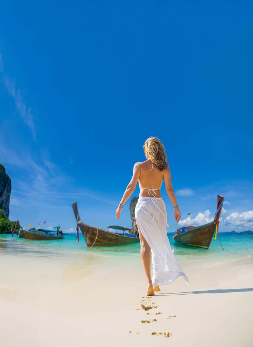 Young blonde woman wearing white bikini and white sarong walking on a white sand beach towards two Thai boats in the ocean