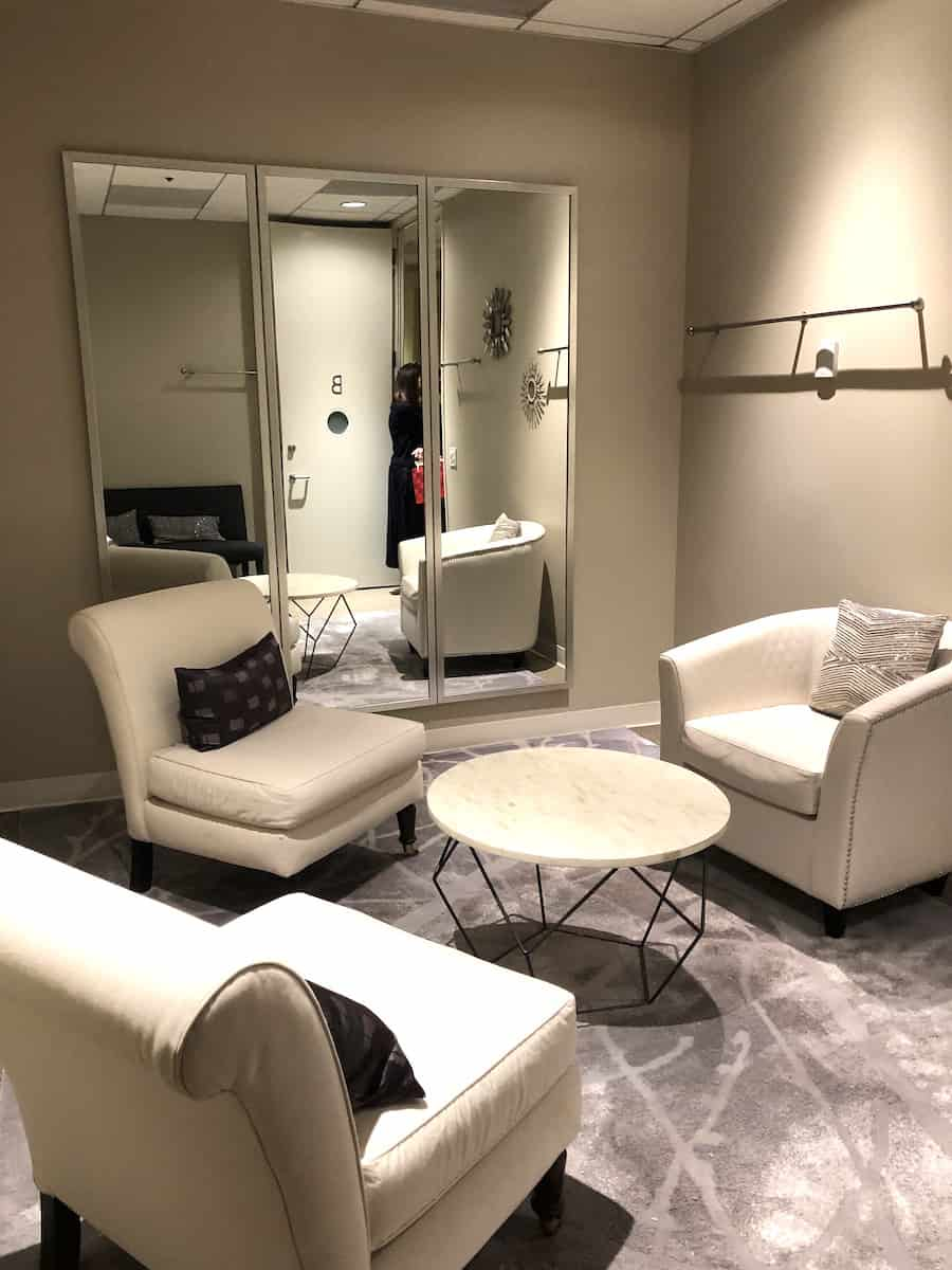 access suite lounge stylist room with three white leather chairs and clothes rod on wall