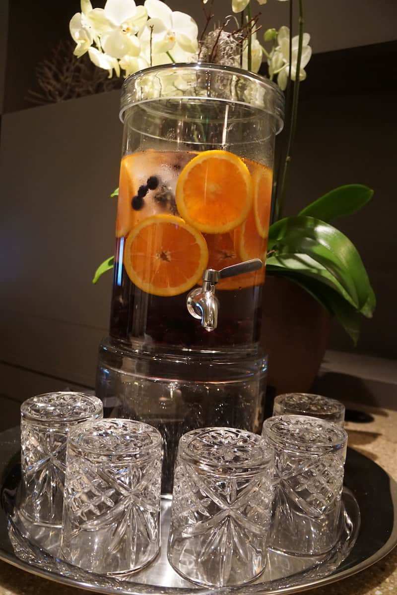 Clear jar of water with orange slices and blueberrys and crystal drinking glasses at access suite lounge