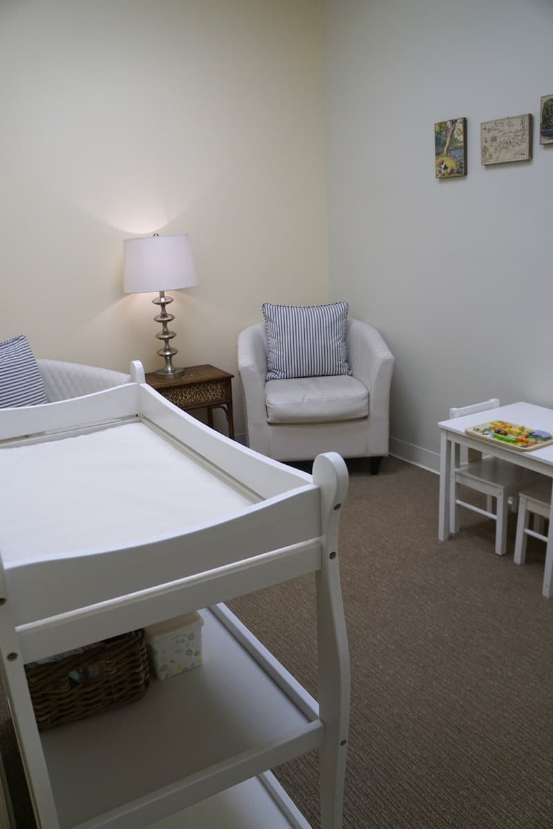 room in the south coast plaza access lounge with white changing table, two white leather chairs, a small white childrens desk and chairs