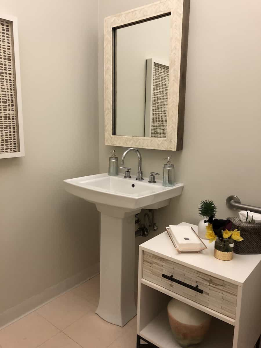 white sink, mirror, and table in access suite lounge bathroom