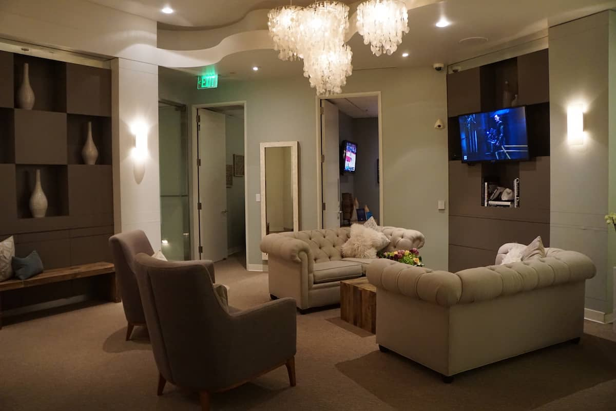 two plush neutral colored loveseats with decorative pillows, two padded chairs, a wood coffee, and wall-mounted TV
