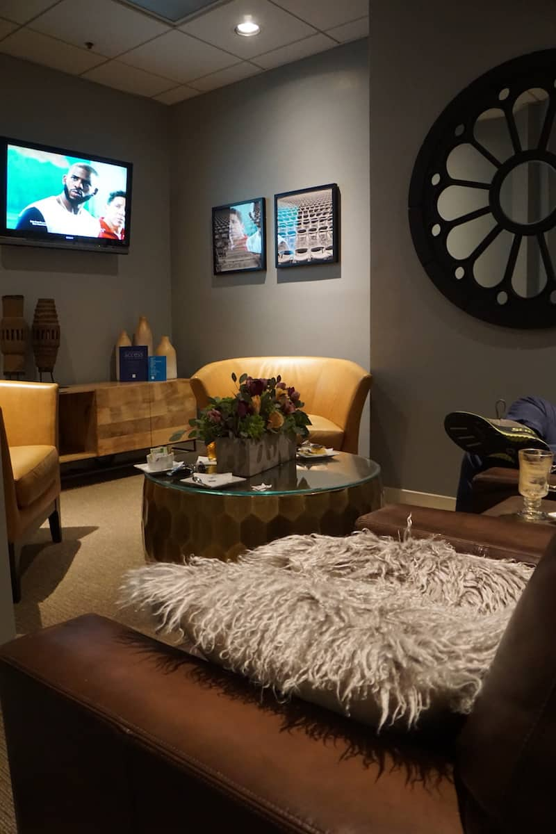 three leather chairs, a table, a sideboard, and a TV