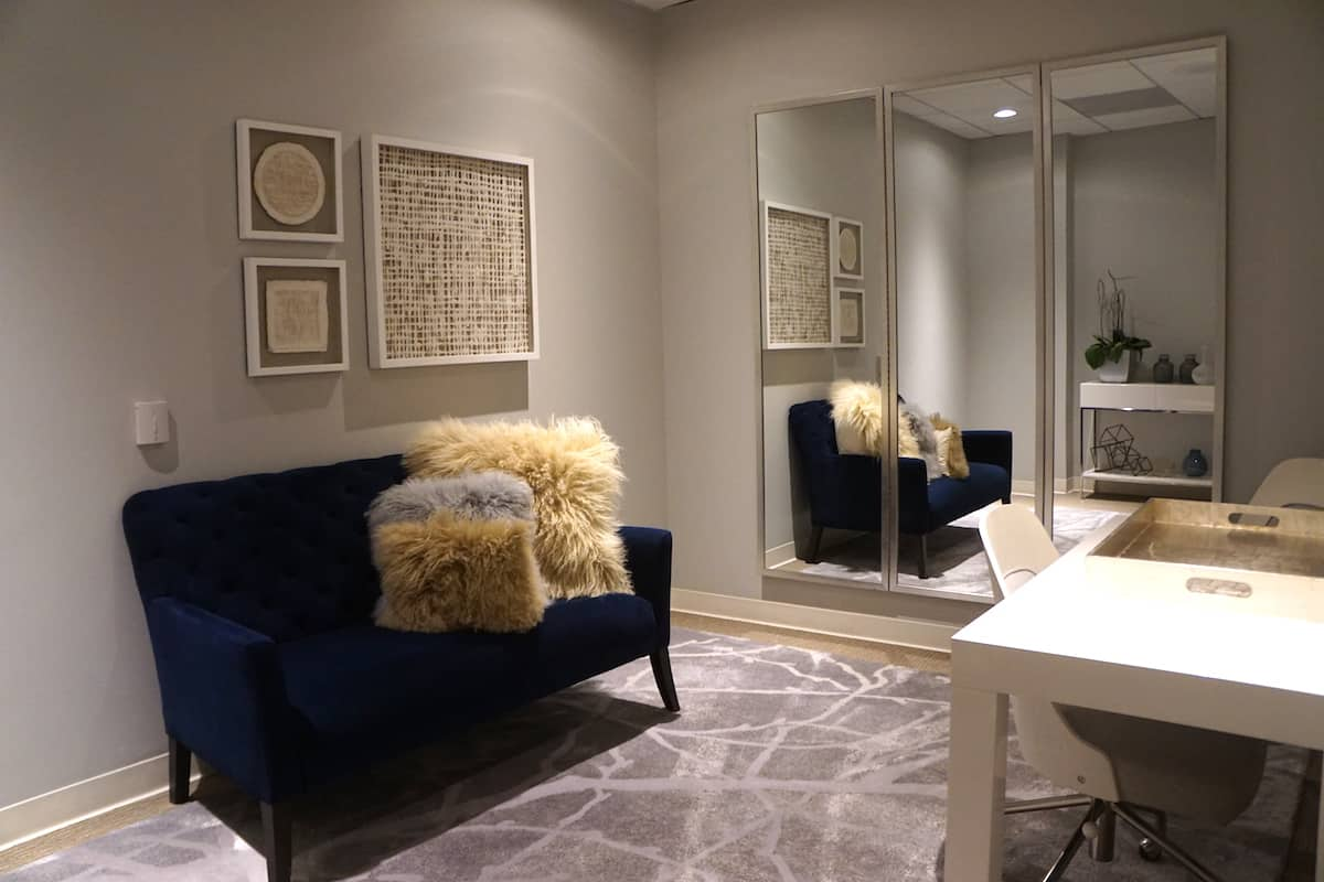 blue velour love seat with faux sheepskin pillows in access suite lounge stylist room a
