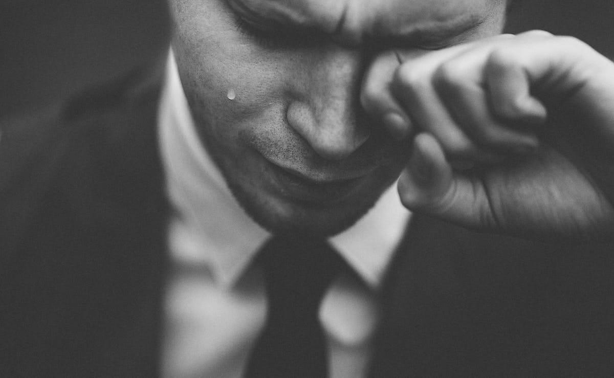 man in black suit wiping his tears