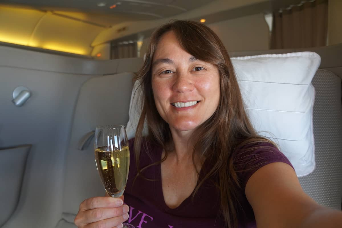 young woman holding glass of Krug champagne in Cathay Pacific First Class