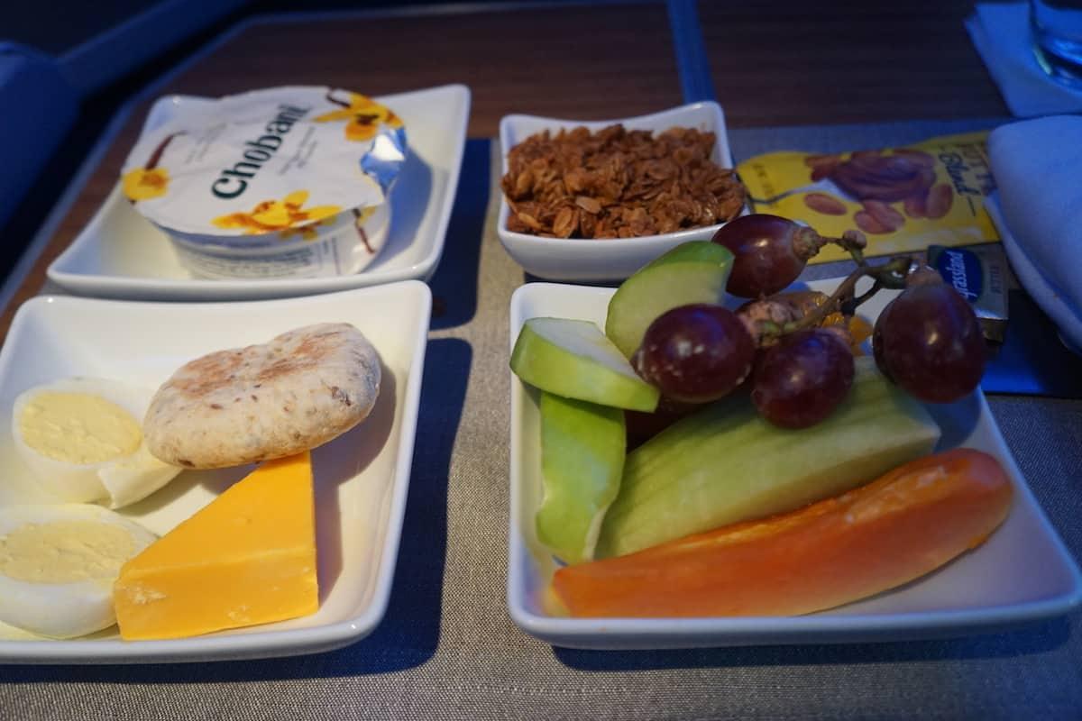 healthy breakfast of yogurt, granola, cheese, fruit on airplane