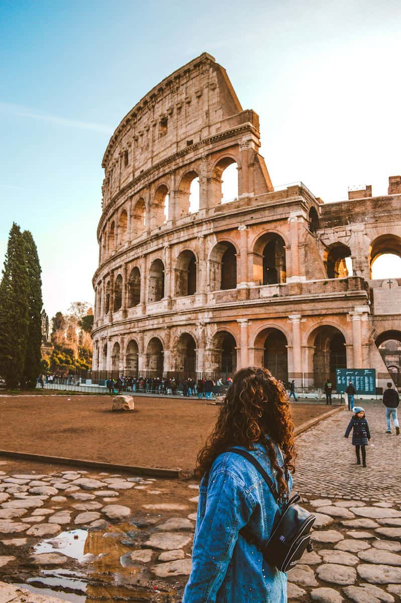 woman with long curly dark hair wearing blue jean jacket standing near Colosseum, Rome