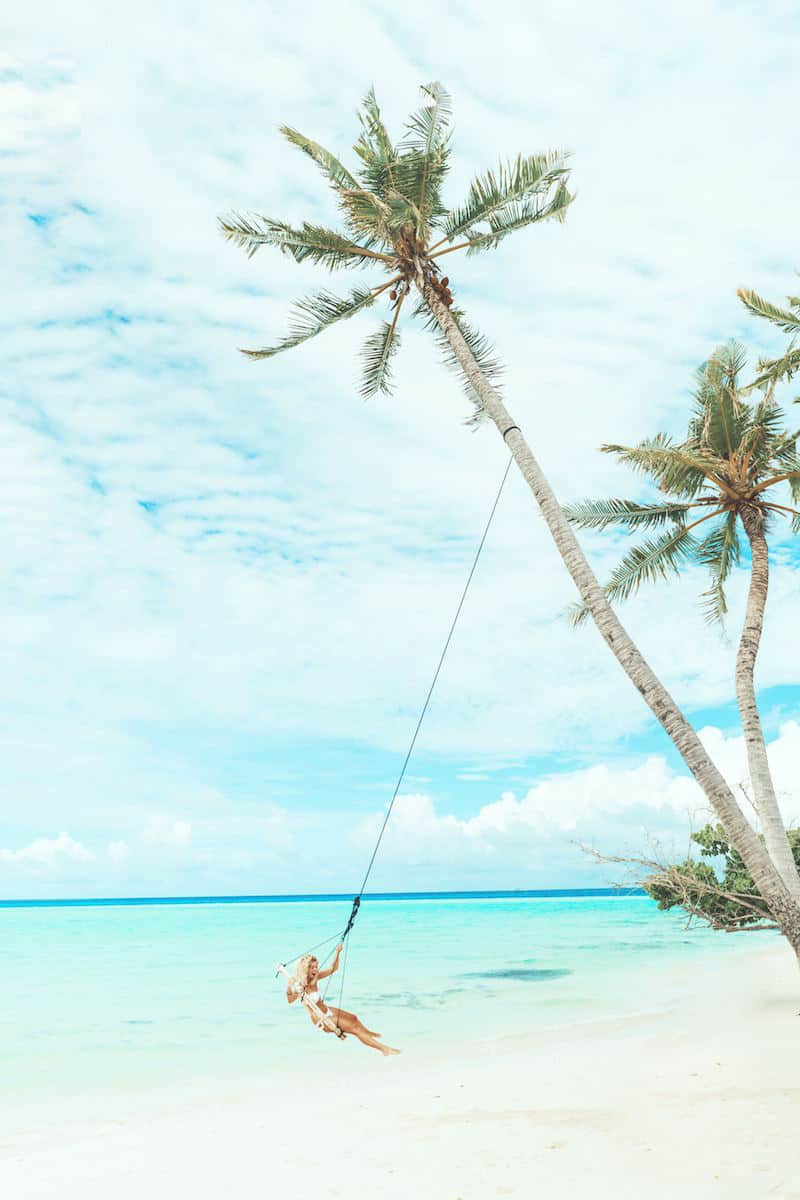 young blonde woman on beach palm tree swing