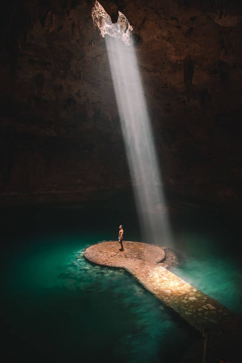 man standing in xenote cave in tulum