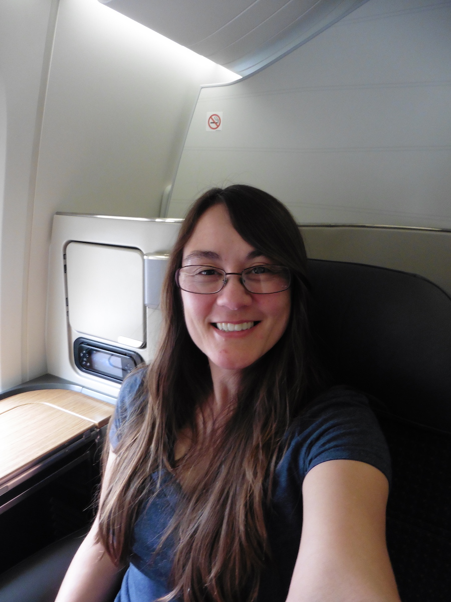 woman with brown hair sitting in First Class, Debra Schroeder flying American Airlines First Class from LHR to LAX