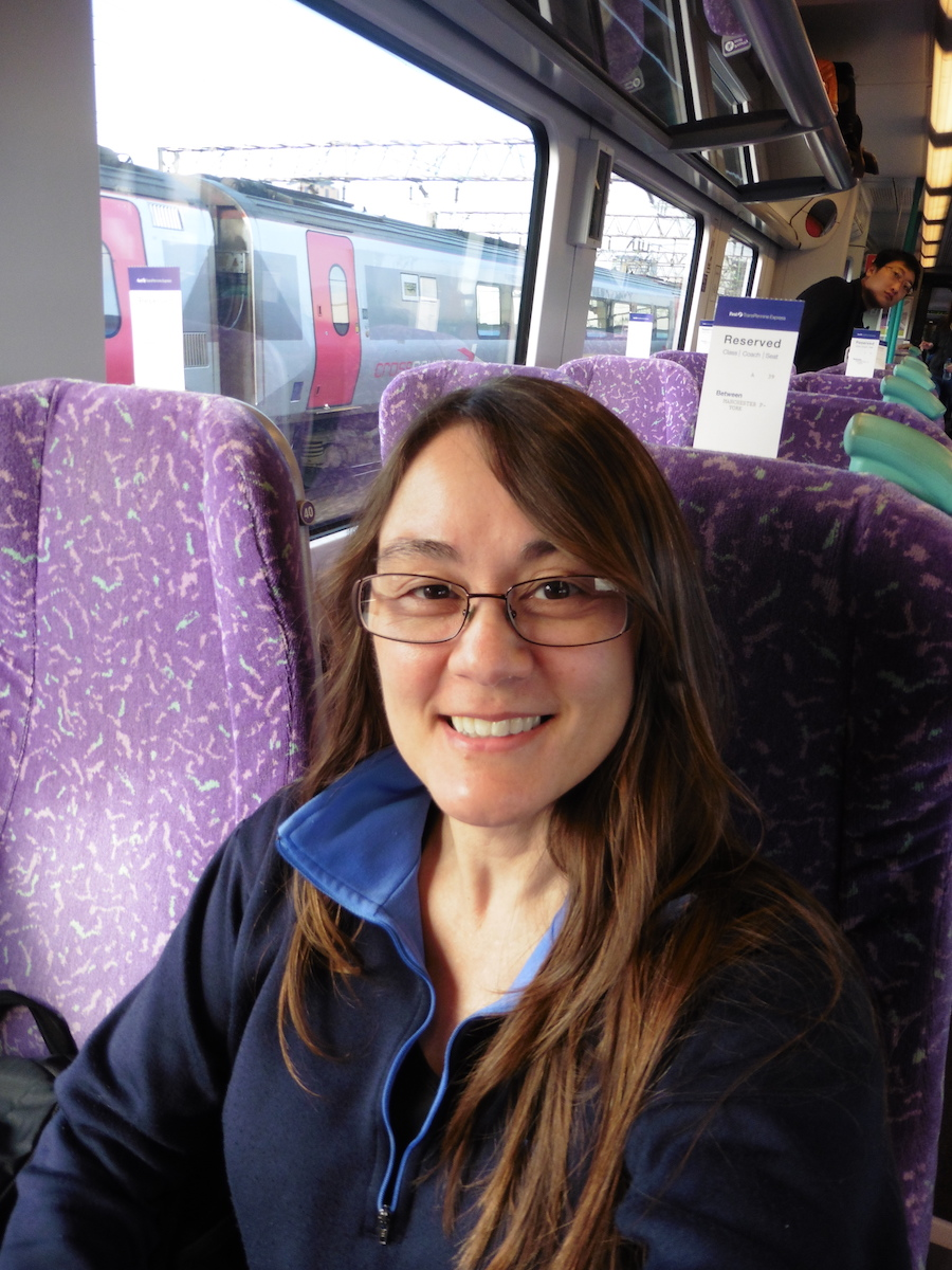 woman with brown hair and glasses riding purple chaired train, Debra Schroeder taking train from Manchester to Edinburgh in coach