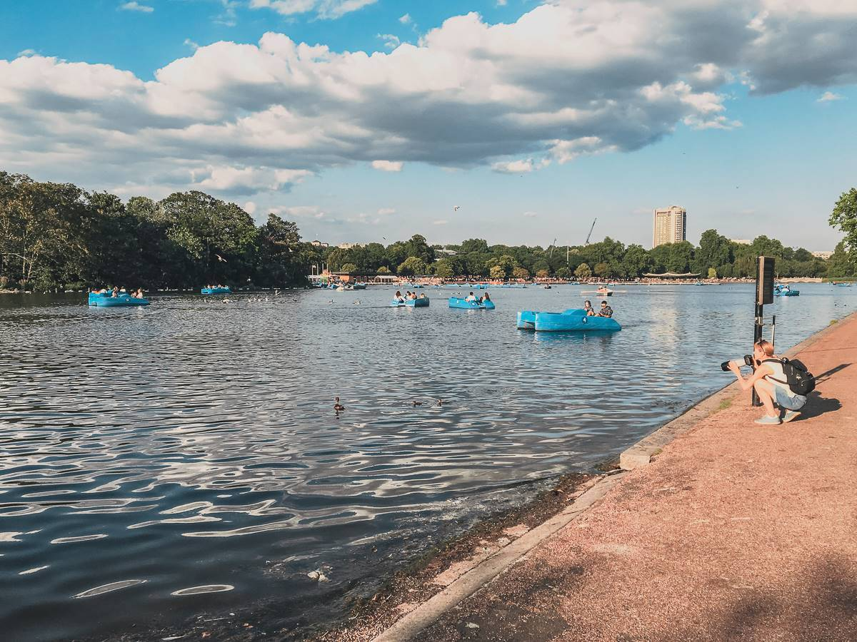 people in blue pedal boats on lake at hyde park london