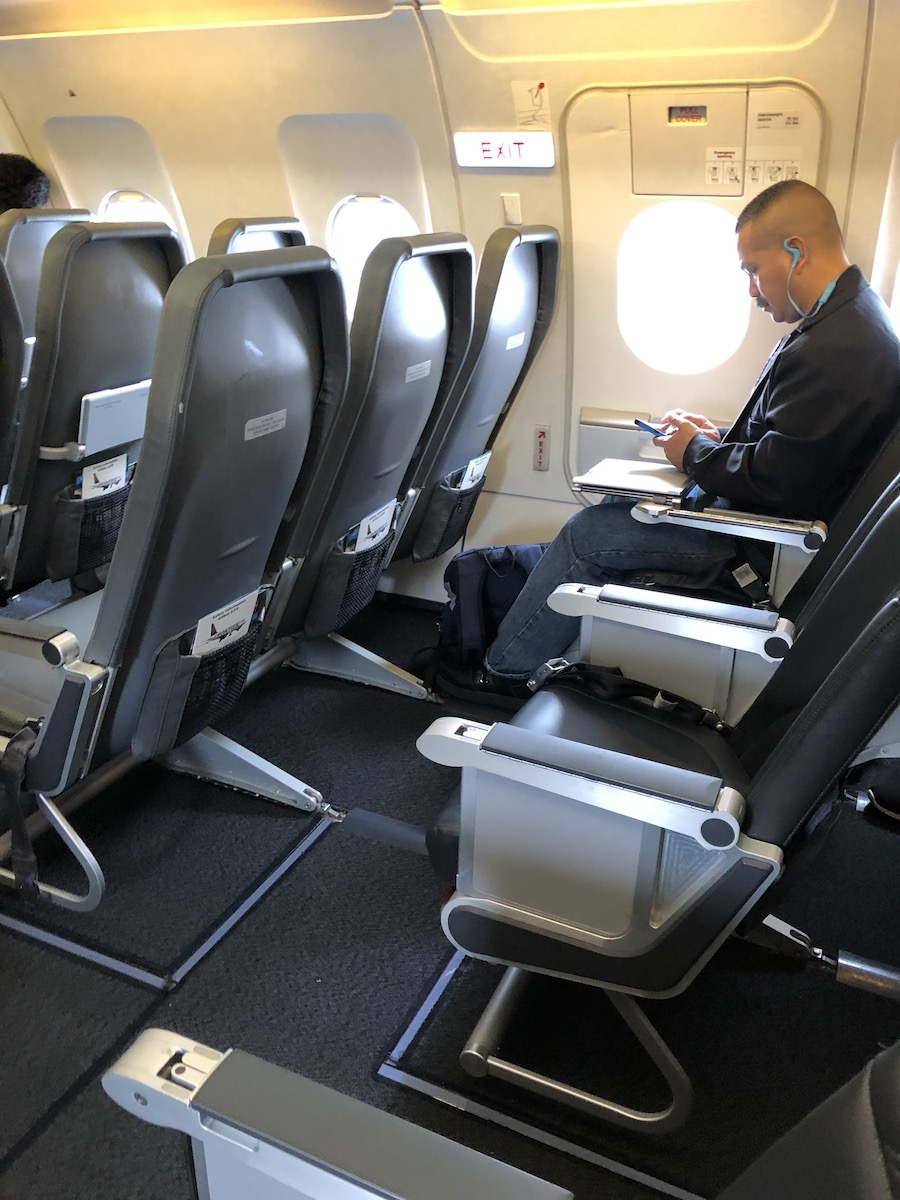 man sitting in window seat in exit row on airplane