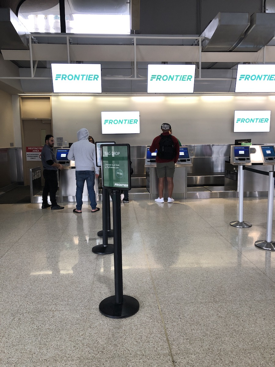people waiting in line at Frontier Airlines counter at San Diego airport
