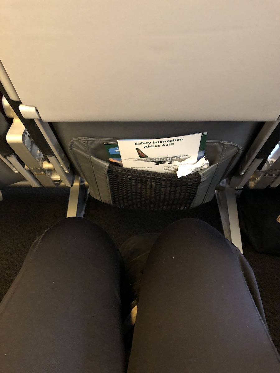 legs of woman wearing black pants sitting in an airline seat with decent leg room