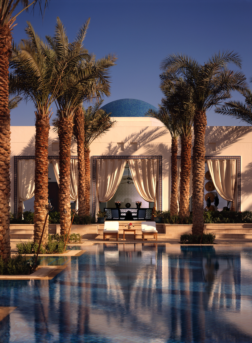pool chairs and cabana by palm tree lined pool at Park Hyatt Dubai