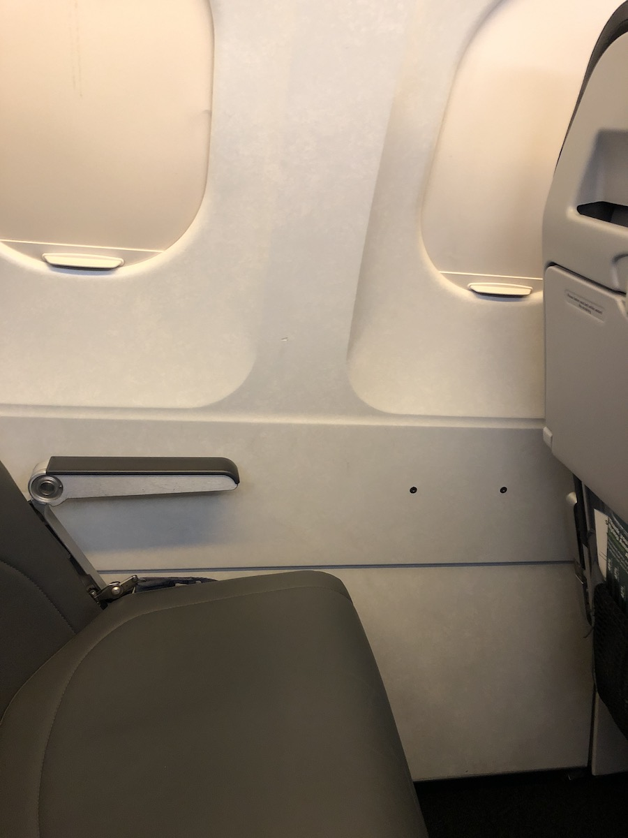 empty seat and closed window shades on airplane