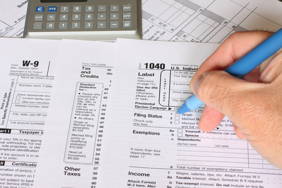 a single man filling federal tax forms with a pen