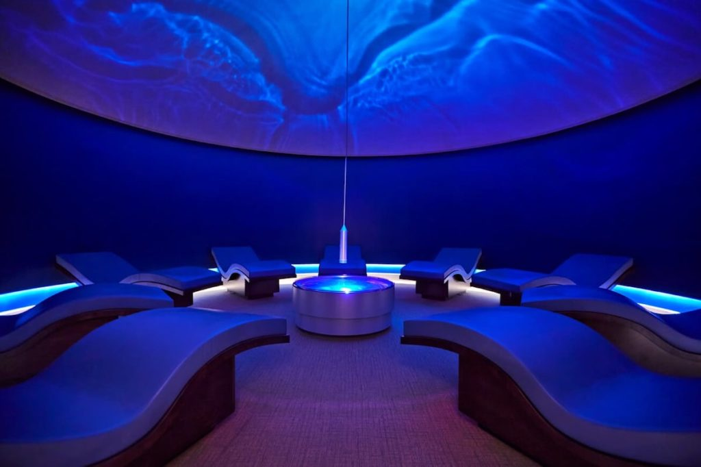 nine s-shaped lounge chairs in a domed blue-tinted relaxation room at Canyon Ranch Spa Las Vegas where waves are projected on the ceiling