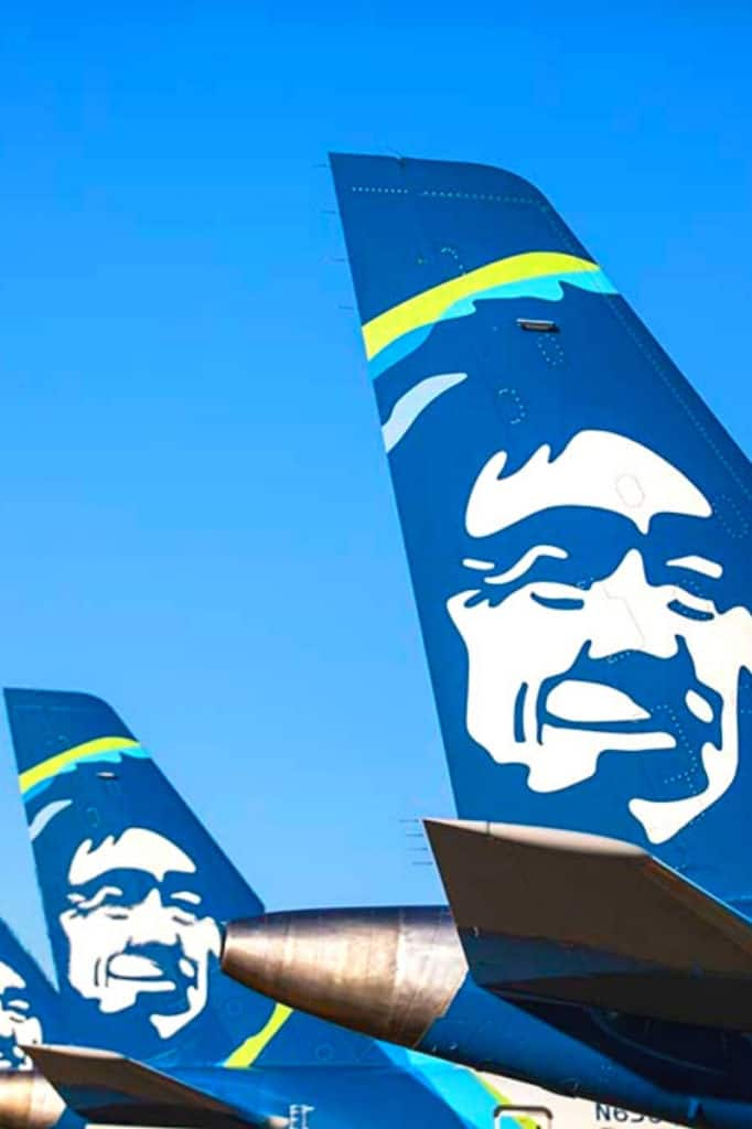 Tail of three Alaska Airlines planes lined in a row