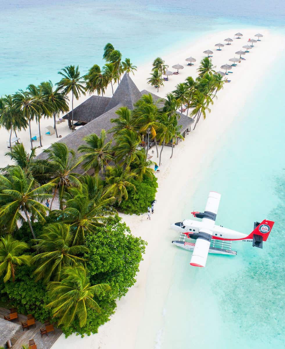 red and white small plane flying over beach front tropical resort