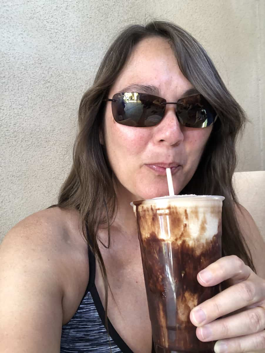 girl wearing sunglasses sipping chocolate drink