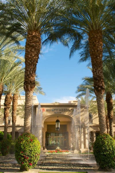 palm tree lined front of hotel