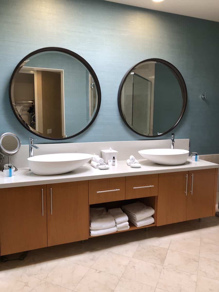 bathroom with two round mirrors and oblong countertop sinks