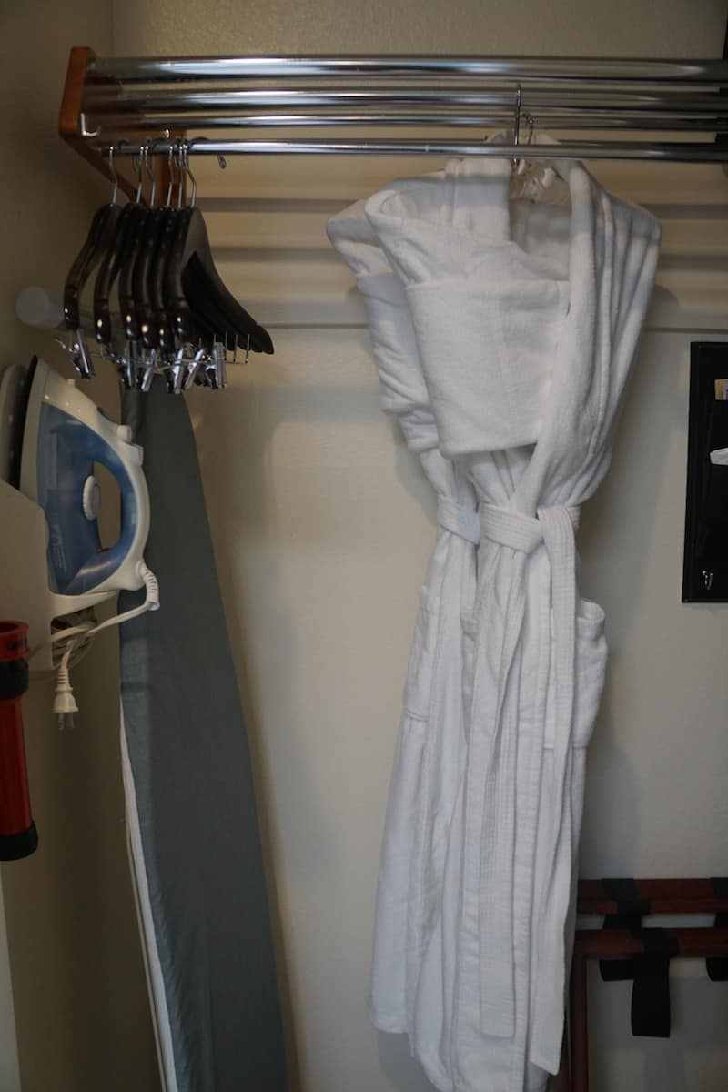 closet with iron, ironing board, and two white robes
